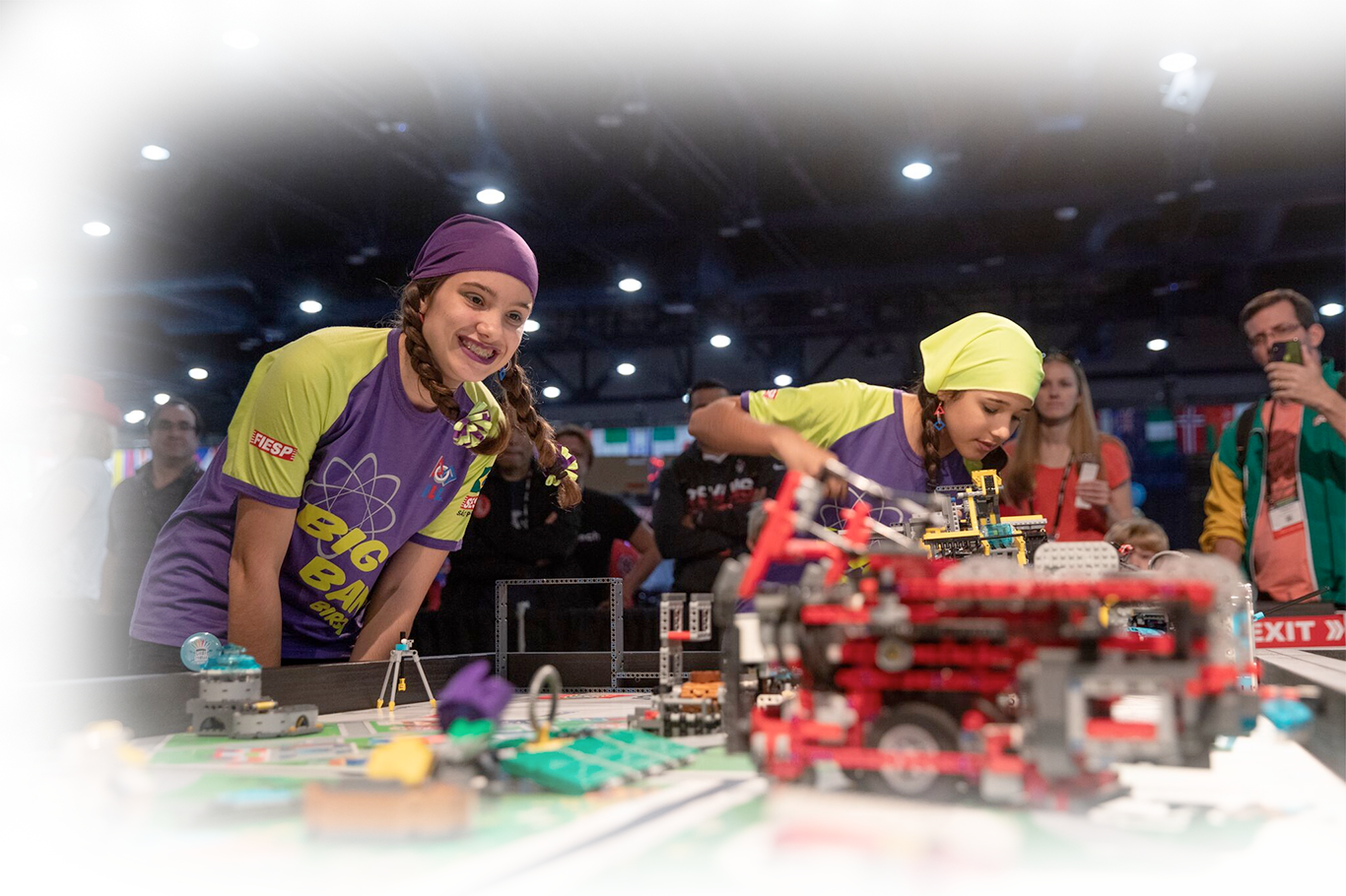 Students competing with LEGO robots at an event.