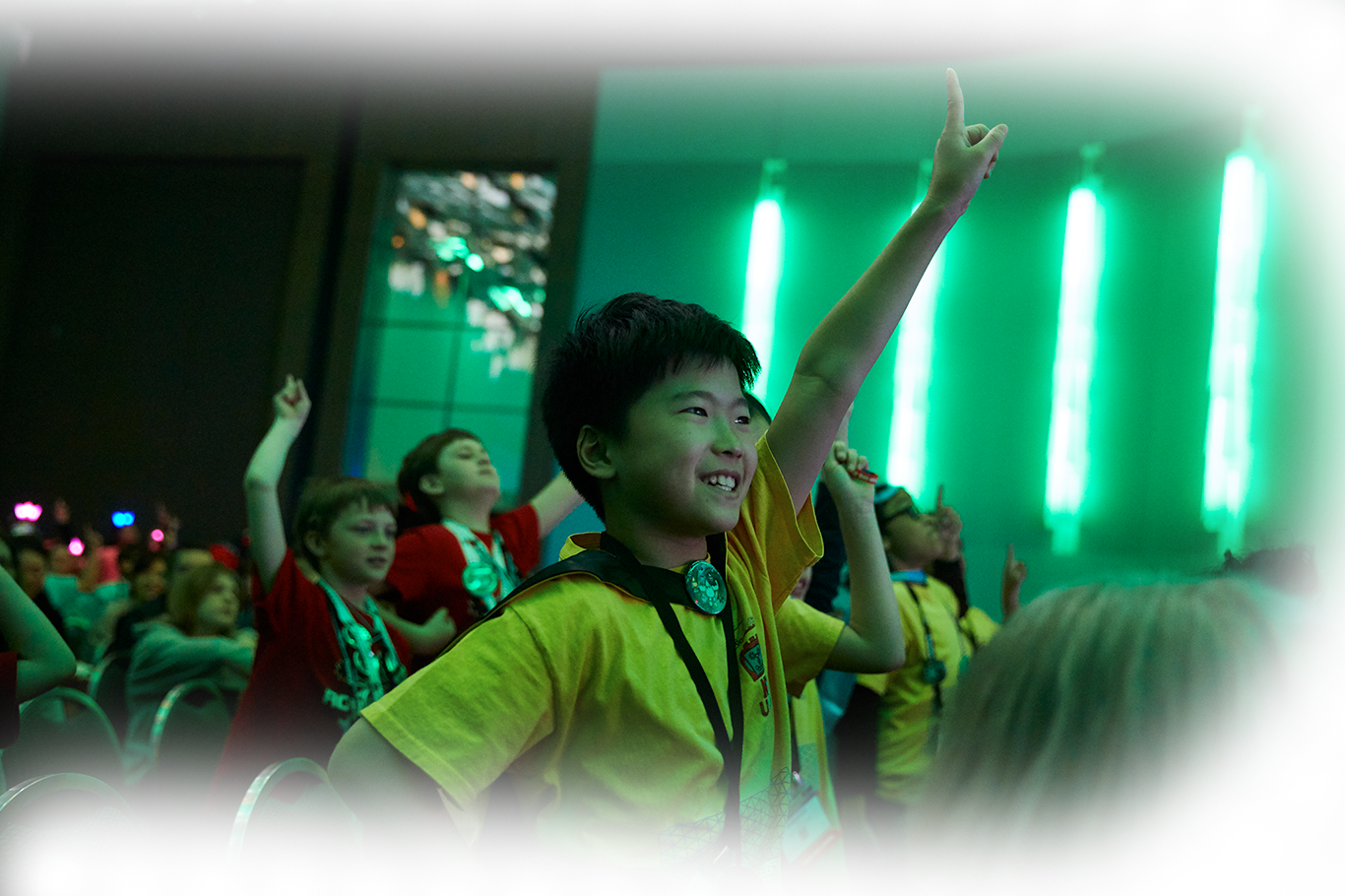Young kid cheering at FIRST LEGO League event.