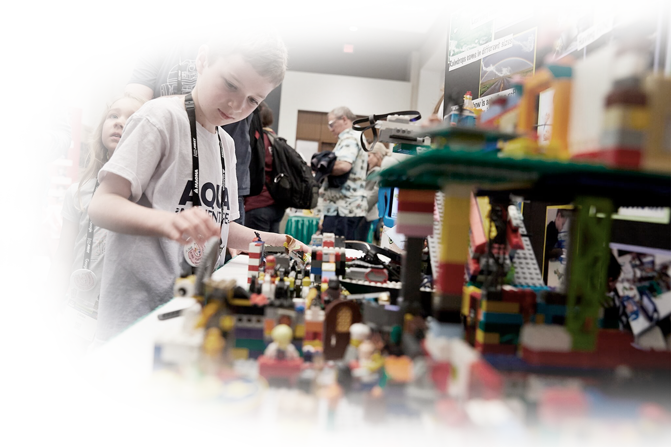 Young student working on LEGO model at FIRST event.