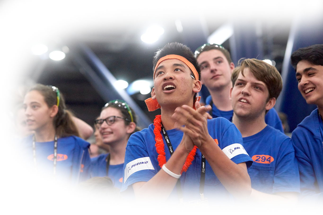 Student team members cheering at FIRST Robotics Competition field.