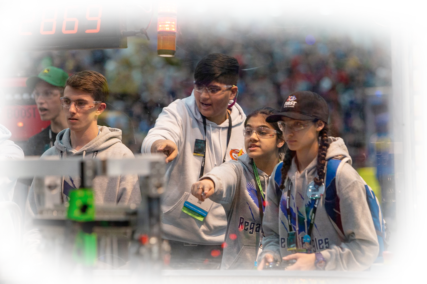 Students playing robotics game on competition field