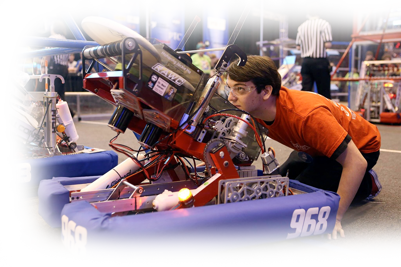 Student working with robot on competition field