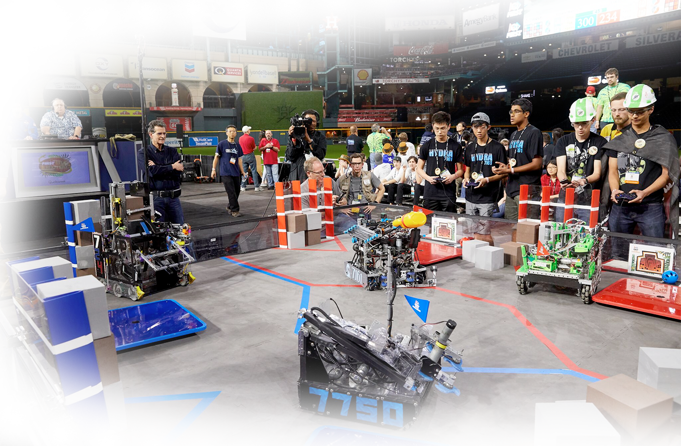 Students competing in robotics game on a playing field.